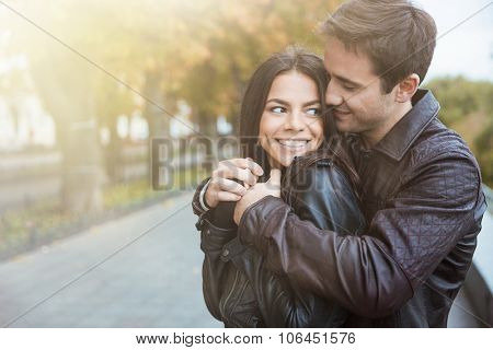 Portrait of a happy young couple flirting in autumn park