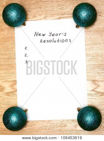 New Year's Resolutions On A Blank List On Wooden Background / With New Year Bright Pink Balls