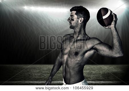 Shirtless rugby player ready to throw the ball against spotlight