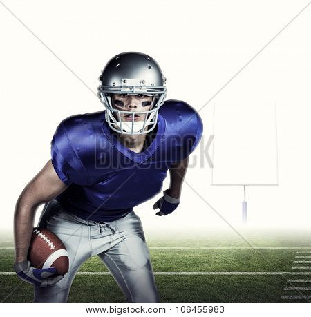 Portrait of American football player in uniform playing against american football posts