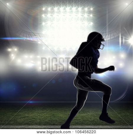Silhouette American football player runing against american football arena