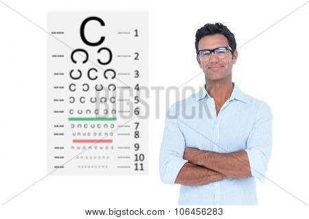 Confident man standing with arms crossed against eye test
