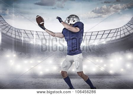 American football player catching ball against rugby stadium