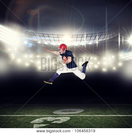American football player jumping with the ball against american football arena