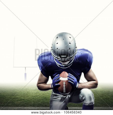 American football player kneeling against american football posts