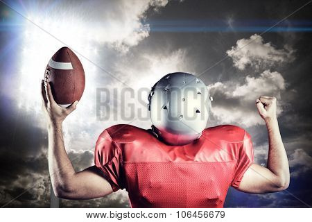 Rear view of American football player cheering while holding ball against spotlight in sky