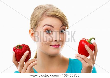 Disgusted Woman Holding In Hand Old Wrinkled And Fresh Peppers, White Background