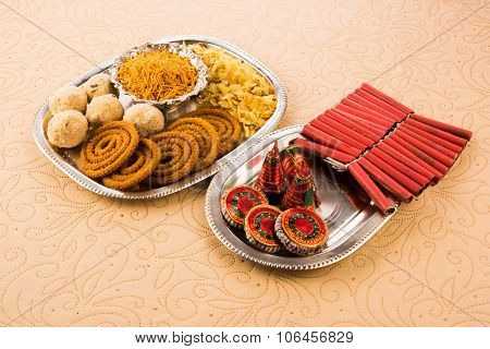 diwali crackers with diwali snacks or diwali food or diwali sweets in silver plate, diwali concept,