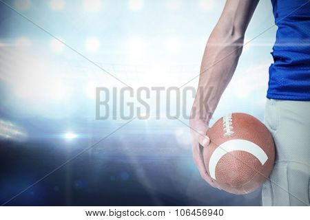 Midsection of sports player holding ball against american football arena