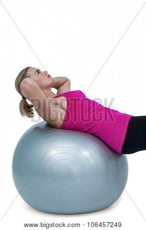 Muscular woman exercising on ball against white bakground