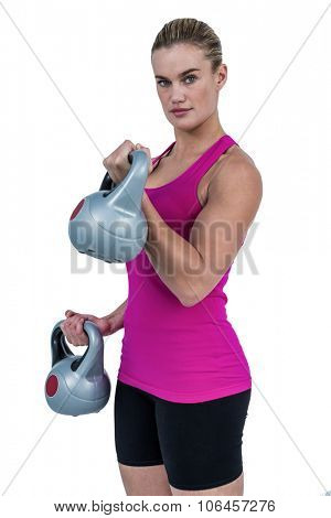 Muscular woman exercising with kettlebells on white background