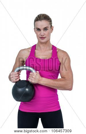 Muscular woman exercising with kettlebell on white background