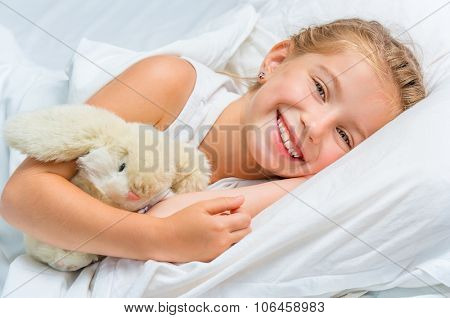 cute smiling little girl woke up in white bed