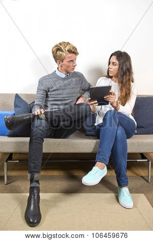 Young man and woamn, sitting on a couch in a living room, surfing together on a tablet. The woman is showing him something online.
