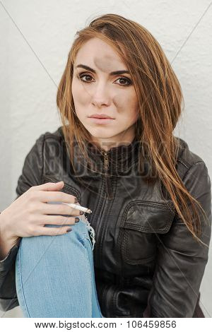 Sad long-haired girl in leather jacket with a cigarette