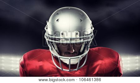 Close-up of serious American football player in red jersey looking down against spotlight