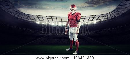 Portrait of american football player holding football against rugby stadium