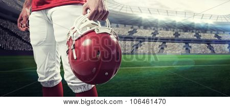 An american football player taking his helmet on her hand against rugby stadium