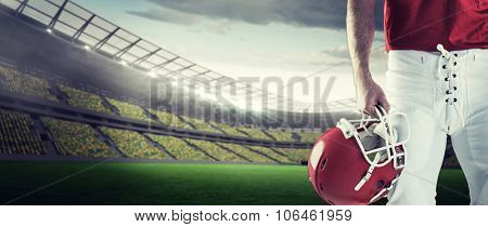 Front view of American football player holding his helmet against rugby stadium