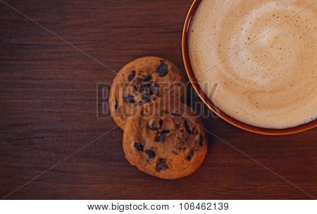 Cup of coffee with milk foam and  cookies with chocolate crumbs on wooden background, close up upside view