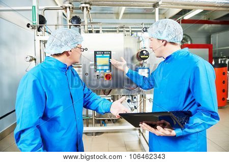 Two pharmaceutical male workers operating air conditioning equipment at pharmacy industry manufacture factory using notebook computer