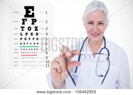 Smiling female optician presenting eye glasses against eye test