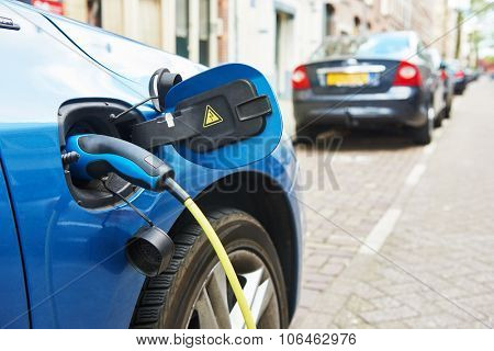 alternative eco energy fuel. Close up of the power supply plugged into an electric car being charged in Amsterdam