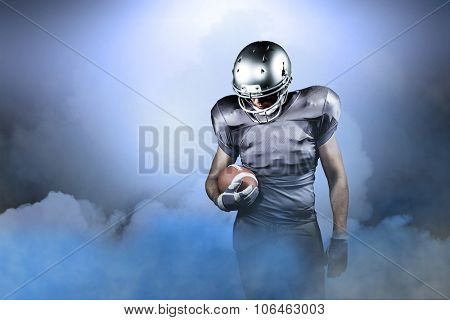 American football player looking down while holding ball against cloudy sky