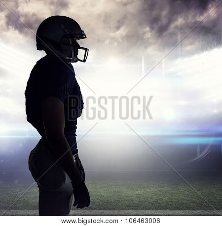 Side view of silhouette American football player standing against american football arena