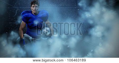 Portrait of serious sportsman with hand on knee holding helmet against dark grey room