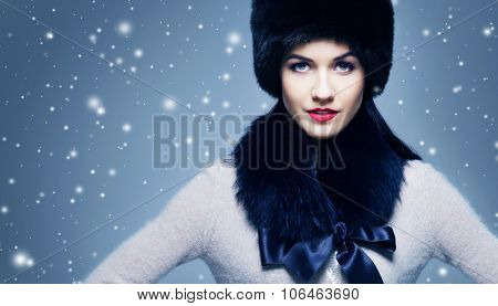 Fashion style portrait of a woman in an elegant winter fury clothes over snowy background.