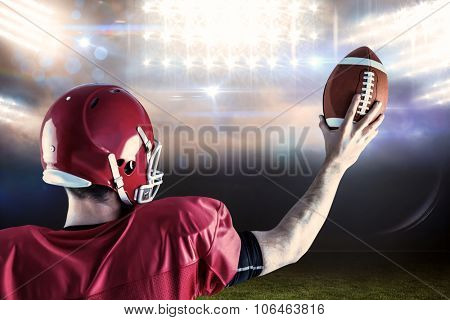 Rear view of american football player holding up football against sports pitch