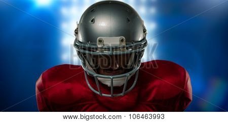 Close-up of serious American football player in red jersey looking down against spotlights