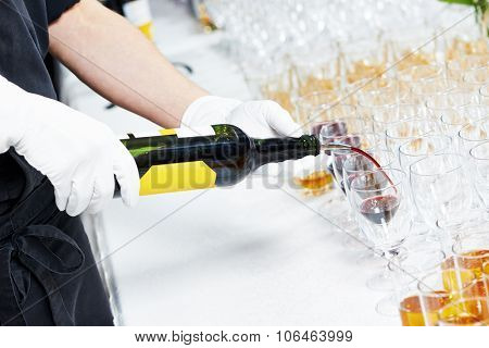 Catering or celebration concept. Male waiter hand pouring  glass of red wine during catering service at party