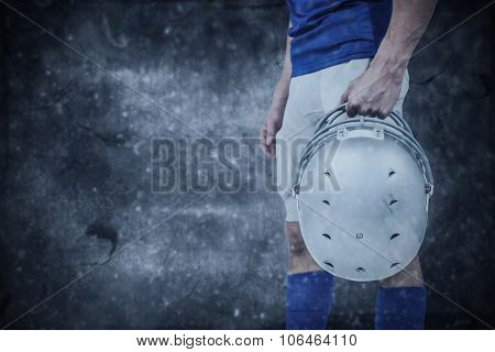 Sports player handing his helmet against dark background
