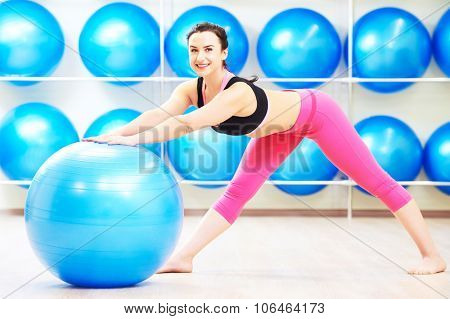 beautiful smiling woman  doing warm up exercise with fitness ball for balance in sport club