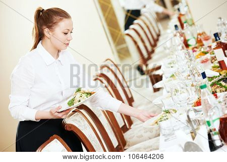 Restaurant catering services. Waitress with salad dish serving banquet table
