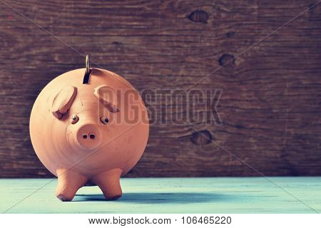 an earthenware piggy bank with a coin in his hole, on a blue rustic surface