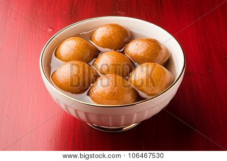 indian sweet gulab jamun dipped in a sweet syrup in white ceramic bowl on red wooden background, iso