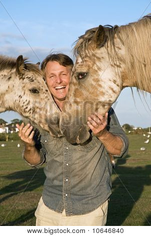 A happy man petting his horses