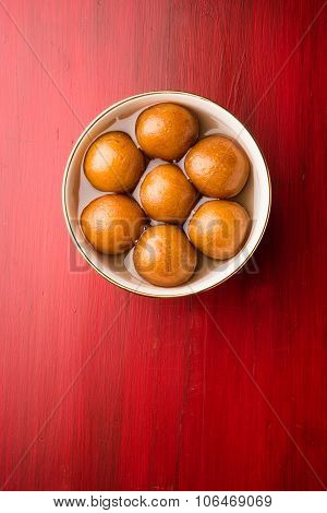 Indian sweet gulab jamun dipped in sweet syrup, in white ceramic bowl, top view, isolated on red woo