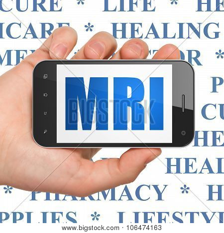 Healthcare concept: Hand Holding Smartphone with MRI on display