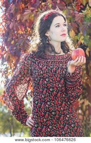Portrait Of Standing Autumn Girl In Fall Head Wreath With Red Apple In Arm