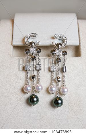 Luxury earrings made of white gold with diamonds and perls on a stand.
