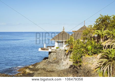 Huts With Thatched Roofs On The Edge Of A Cliff By The Sea, Costa Adeje, Tenerife