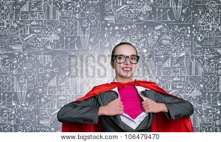 Young businesswoman in red cape acting like super hero and sketches on background