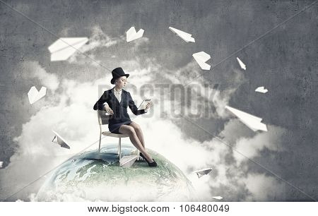 Pretty girl wearing retro hat siting on chair with tablet in hand. Elements of this image are furnished by NASA