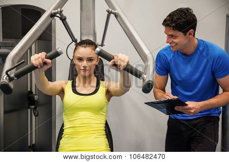 Confident woman using weights machine with trainer at the gym
