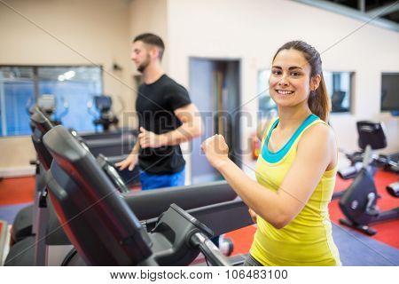 Man and woman using treadmills at the gym