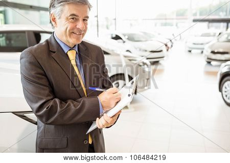 Portrait of a salesman with clipboard at new car showroom